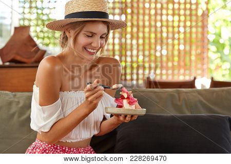 Portrait Of Young Female Model In Fashionable Clothing Wears Straw Hat, Eats Delicious Cake Or Desse