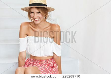 Positive Sunburnt Female Has Happy Expression, Wears White Blouse, Short Polka Dot Skirt And Straw H