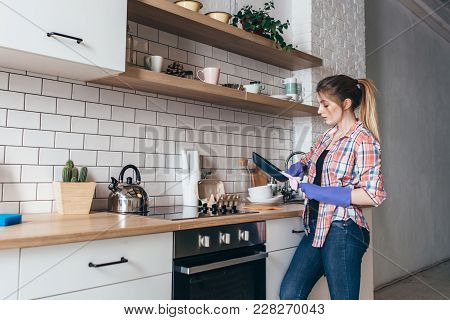 Young Woman Wiping Frying Pan After Washing In Kitchen.