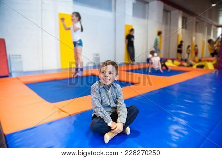 Happy Little Boy Sitting On Trampoline Among Group Of Kids Indoors