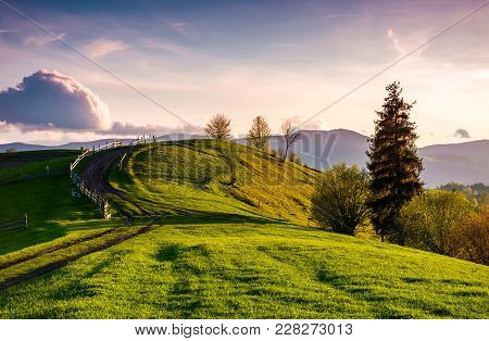 Country Road Through Grassy Hill At Sunset. Lovely Landscape In Mountains Under The Ravishing Evenin