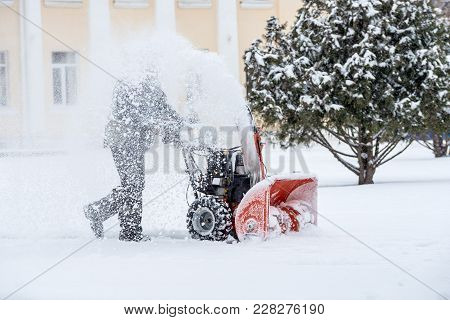 Snow-removal Work With A Snow Blower. Man Removing Snow. Heavy Precipitation And Snow Pile