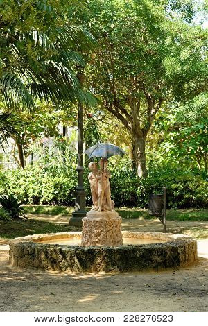 Fountain In Genoves Park, An Exotic Garden Oasis In Cadiz, Andalusia, Spain. It Is Lined With Differ