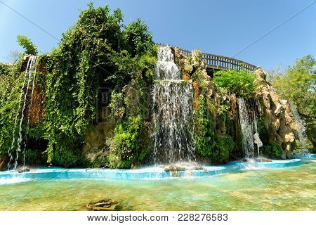 Waterfall In The Duck Pond In Genoves Park, An Exotic Garden Oasis In Cadiz, Andalusia, Spain. It Is