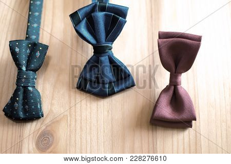 Three Blue And Brown Color Bow Ties On Light Brown Wood Background. Happy Fathers Day Concept.