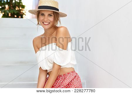 Pleased Beautiful Young Woman With Broad Smile, Dressed In Fashionable Clothing, Has Happy Expressio