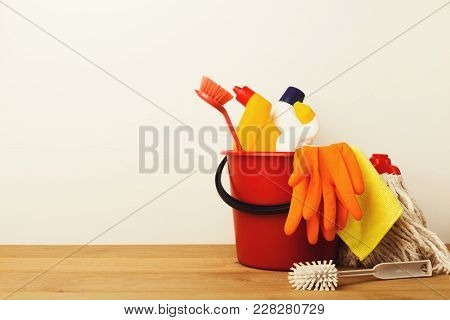 Variety Of House Cleaning Products On Wood Table At White Background, Closeup. Bucket, Brush, Rubber