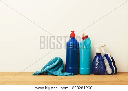 Group Of Blue Bottles, Cleaning Products, Rag And Brush On White Background. House Keeping, Tidying