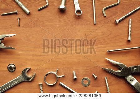 Industrial Metal Tools - Pliers, Screws, Wrench -  On Brown Wooden Background With Copy Space. Top V