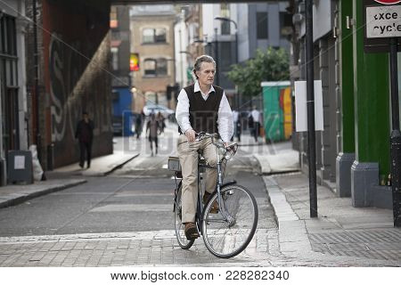 London, England - August 22, 2017 An Elderly Gentleman In A Vest On A Bicycle, Turns On The Main Roa