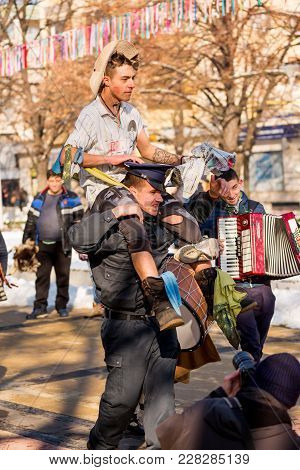 Pernik, Bulgaria - January 26, 2018: Male Dressed As Policeman Carries Funny Citizen With Make-up In
