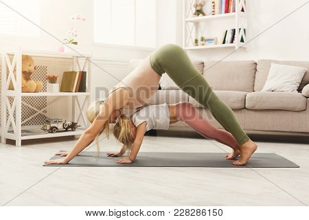 Young Mother And Her Little Daughter Doing Back Stretching Yoga Exercises At Home. Sporty Family Lif