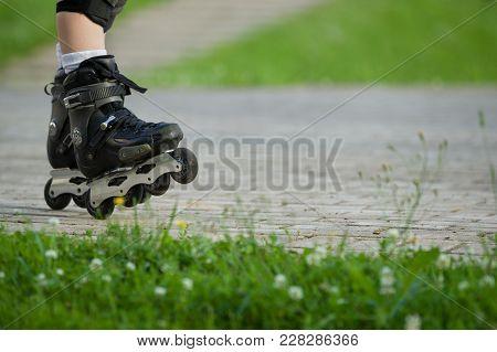 Black Roller Skates. Closeup Of Rollerblading. Roller Skater's Legs In The Park. Boy's Legs In Rolle