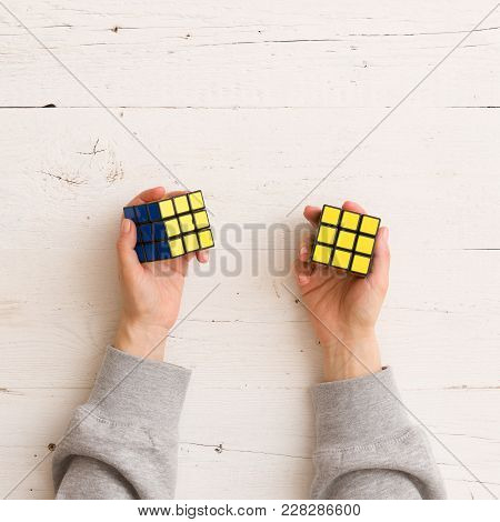 Moscow, Russia, February 16 2018: Rubik's Cube In Woman's Hands, Closeup, White Wooden Background. G