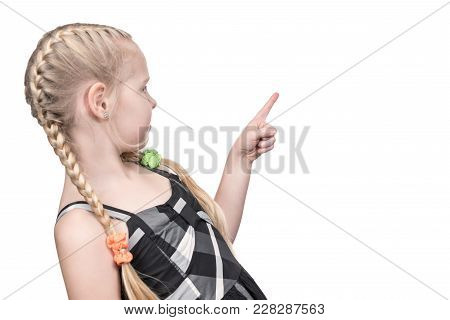 Child Girl Stands Sideways To The Camera And Points Finger Back And Sideways Isolated On White Backg