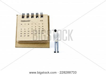 February. Two Thousand Eighteen Year Calendar And Miniature Plastic Man On White Background.