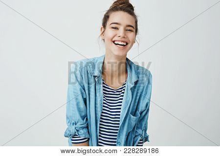 Girl Likes Funny Jokes. Smart Good-looking Student With Bun Hairstyle Trembling From Laugh, Smiling