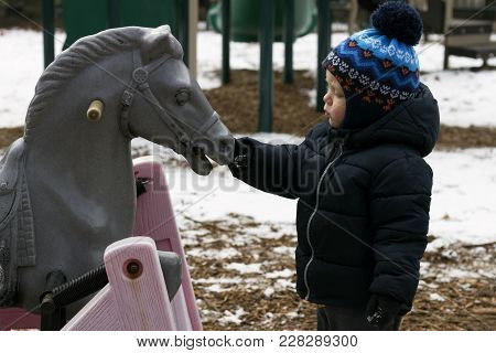 Two Year Toddler Playing With A Toy Horse. Kid Feeding Wooden Horse.