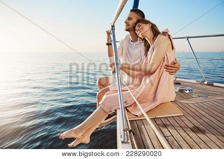 Happy Beautiful Adult Couple Sitting On Side Of Yacht, Watching At Seaside And Hugging While On Vaca