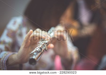 A Woman Is Playing  Flute.