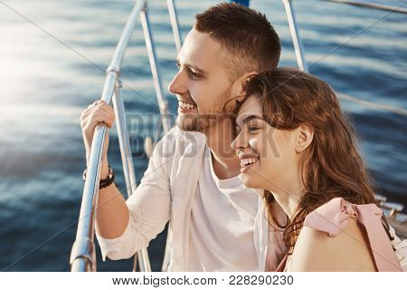 Two Beautiful Married People In Love, Smiling Broadly While Sitting At Bow Of Boat And Holding Handr