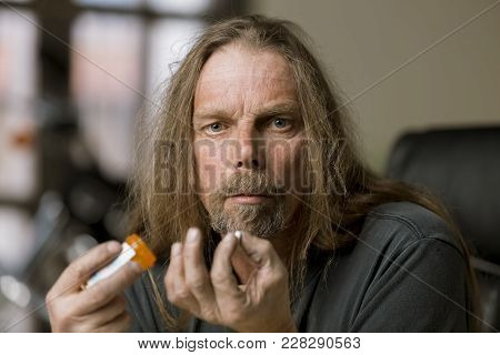 Addicted Man Holding An Opioid Pill Bottle