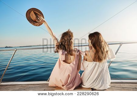 Back Portrait Of Two Female Friends Sitting On Boat, Waving With Hat While Talking And Enjoying Look