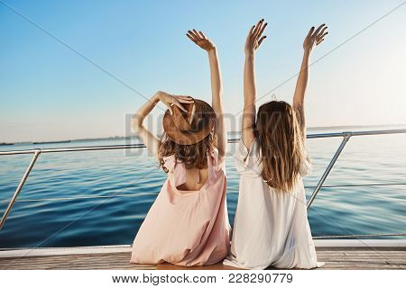 Outdoor Back Shot Of Two Young Female On Luxury Vacation, Waving At Seaside While Sitting On Yacht.