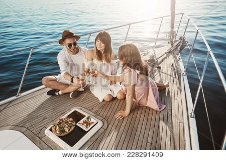 Portrait Of Stylish Good-looking European People Having Lunch On Board Of Yacht, Drinking Vine And E