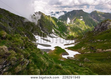 Valley With Snow In Summer Mountains. Gorgeous Mountainous Landscape Of Carpathians. Rocky Cliffs An