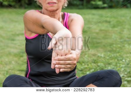 Senior Woman Is Showing Exercise For Pain Relief. Forearm Stretching For Carpal Tunnel Syndrome Pain