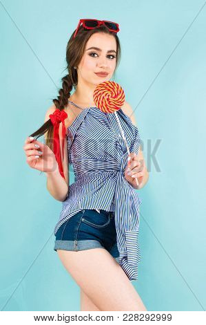 Portrait Of Brunette Young Pin-up Woman In Striped Shirt And Jeans With Sunglasses Isolated On Blue