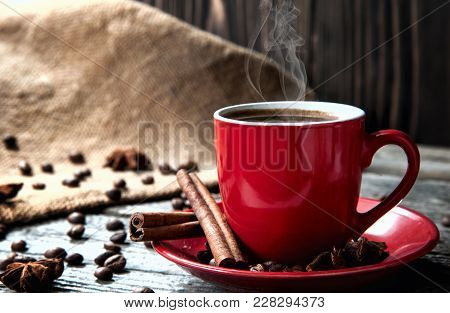 Coffe In Red Mug On Wood Table With Coffee Beans And Cinnamon Closeup