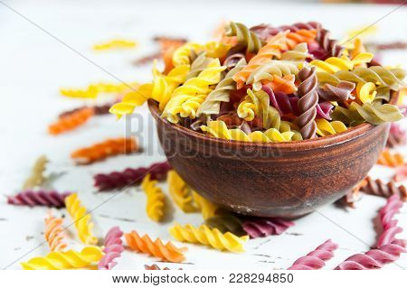 Assortment Of Colorful Pasta In Color Bowls On On Whita Wooden Background