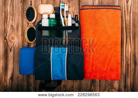 Top View Of Kit For Hygiene During Hiking And Travel On Wooden Table With Empty Space. Items Include