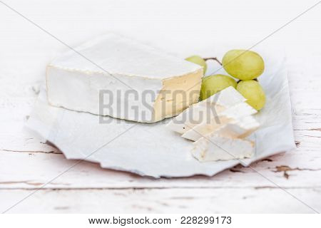 Fresh Brie Cheese With Slices And Grape On White Rustic On A Wooden Board. Brie Type Of Cheese.  Cam