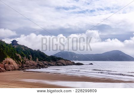 A Chinese Building And Rocky Shore At 100 Step Beach At Low Tide On The Island Of Putuoshan China On
