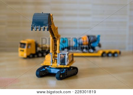 Toy Excavator With Raised Bucket. Blurred Background With Transport Truck With Concrete Mixer