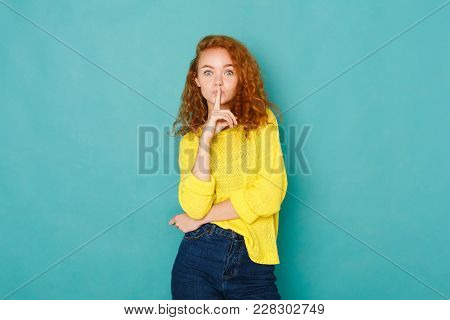 Keep Silence. Astonished Redhead Woman With A Finger On Her Lips Showing To Keep Quiet, Hush, Posing