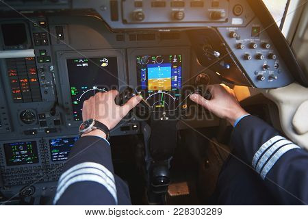 Close Up Aviator Arms Navigating Aircraft In Cabin. Appliance And Aviation Concept