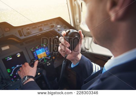 Close Up Pilot Hand Taking By Portable Radio Set In Cabin While Navigating Plane. Occupation And Com