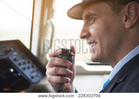 Side View Smiling Aviator Speaking By Portable Transmitter In Cockpit. Communication And Labor Conce