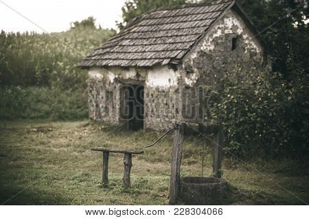 House Barrack With Old Well In Yard. Rural Lifestyle, Countryside. Decay, Decline, Ruins. Architectu