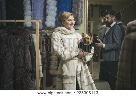 Expensive Clothes And Money Concept. Couple Shopping In Fur Mall. Woman In Fur Coat With Dog And Bea