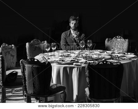 Handsome Young Man With Beard And Blond Hair Drinks Wine From Glass Sitting At Table With Leftovers