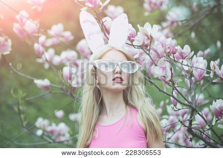 Sensual Woman In Magnolia Bloom. Sensual Sexy Woman In Bunny Ears And Glasses At Magnolia Flower