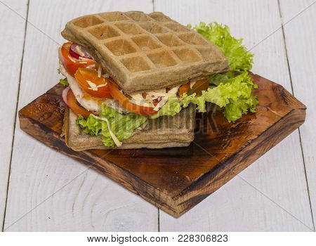 Waffles Sandwich With Chicken, Vegetables And Cheese On Wooden Background. Food, Snack, Meal. Cuisin
