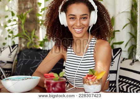 Beautiful Positive African American Woman Enjoys Listening Music In Headphones, Spends Leisure Time