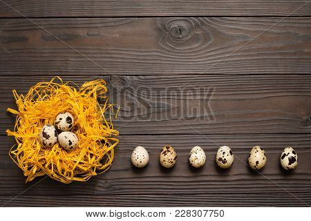 Quail Eggs In The Decorative Nest And A Number Of Quail Eggs On Dark Wooden Background. The View Fro
