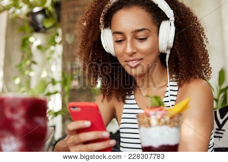 African American Female Student Listens Audio Lesson In Modern Headphones On Smart Phone, Connected